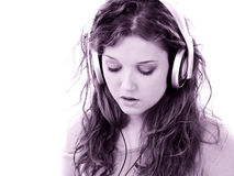 Bella ragazza teenager con le cuffie ed il computer portatile fotografia stock libera da diritti