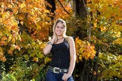 Bella ragazza teenager del paese fra il fogliame di caduta Immagini Stock Libere da Diritti