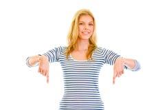 Bella ragazza teenager sorridente che indica le barrette giù fotografia stock libera da diritti