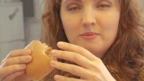 Bella ragazza temptingly che mangia hamburger e che beve soda archivi video