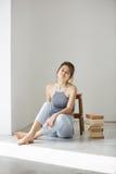 Bella ragazza tenera che sorride esaminando macchina fotografica che si siede sul pavimento con i libri sopra la parete bianca Fotografie Stock