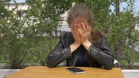 Bella ragazza triste che si siede ad una tavola in un caffè Legge gli sms su uno smartphone Ha abbracci la sua testa con la sua t video d archivio
