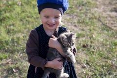 Bella ragazza in un berretto con un gattino grigio sulle sue mani Immagine Stock Libera da Diritti