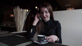 Bella ragazza in un caffè che parla sul telefono e sul caffè bevente archivi video