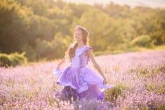 Bella ragazza in un campo di lavanda sul tramonto Immagini Stock