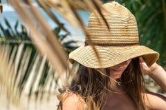 Bella ragazza in un cappello di estate su un fondo delle foglie di palma sopra fotografia stock
