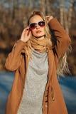 Bella ragazza in un cappotto che posa contro lo sfondo di una natura della molla Immagini Stock
