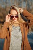 Bella ragazza in un cappotto che posa contro lo sfondo di una natura della molla Fotografia Stock Libera da Diritti