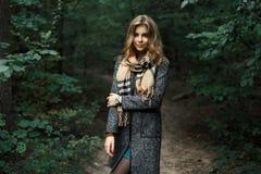 Bella ragazza in un cappotto ed in una sciarpa in una foresta scura immagine stock