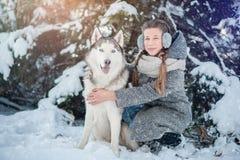Bella ragazza in un cappotto grigio nella foresta di inverno con il husky siberiano Simbolo del nuovo anno 2018 Fotografie Stock