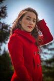 Bella ragazza in un cappotto rosso su un fondo degli alberi fotografia stock libera da diritti