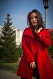 Bella ragazza in un cappotto rosso su un fondo degli alberi fotografie stock