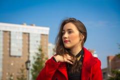 Bella ragazza in un cappotto rosso su un fondo delle case immagine stock
