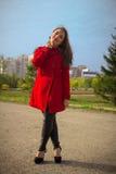 Bella ragazza in un cappotto rosso su un vicolo del parco immagine stock