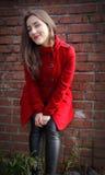 Bella ragazza in un cappotto rosso sul fondo del muro di mattoni fotografie stock libere da diritti