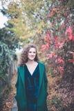 Bella ragazza in un cappotto verde in un parco di autunno immagine stock
