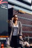 Bella ragazza in un cardigan, in una camicia e negli occhiali da sole all'aperto Fotografia Stock