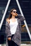 Bella ragazza in un cardigan, in una camicia e negli occhiali da sole all'aperto Immagine Stock
