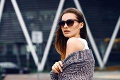 Bella ragazza in un cardigan, in una camicia e negli occhiali da sole all'aperto Immagini Stock