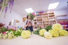 Bella ragazza, un fiorista, selezionante un mazzo dei fiori Immagini Stock