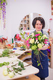 Bella ragazza, un fiorista, selezionante un mazzo dei fiori Immagine Stock