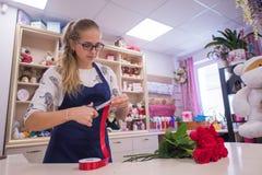 Bella ragazza, un fiorista, selezionante un mazzo dei fiori Fotografia Stock