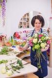 Bella ragazza, un fiorista, selezionante un mazzo dei fiori Fotografie Stock Libere da Diritti