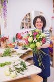 Bella ragazza, un fiorista, selezionante un mazzo dei fiori Immagine Stock Libera da Diritti