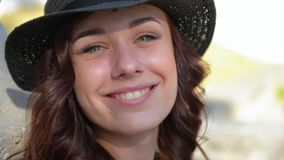 Bella ragazza in un gioco black hat della paglia con i capelli rossi che sorride, ridente e facente un fronte video d archivio