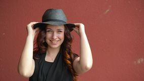 Bella ragazza in un gioco black hat della paglia con i capelli rossi che sorride, ridente e facente un fronte Su un fondo rosso archivi video