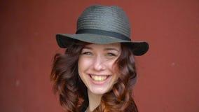 Bella ragazza in un gioco black hat della paglia con i capelli rossi che sorride, ridente e facente un fronte Su un fondo rosso video d archivio