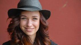 Bella ragazza in un gioco black hat della paglia con i capelli rossi che sorride, ridente e facente un fronte Su un fondo rosso stock footage