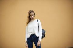 Bella ragazza in un maglione leggero su un fondo giallo della parete Fotografia Stock