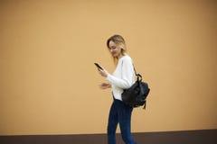 Bella ragazza in un maglione leggero su un fondo giallo della parete facendo uso di collegamento a Internet libero 4G Fotografie Stock Libere da Diritti