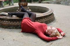 Bella ragazza in un mini vestito rosso alla fontana inaridita Immagini Stock Libere da Diritti