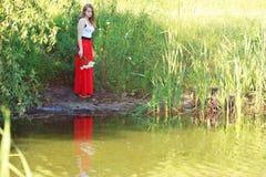 Bella ragazza in un pannello esterno rosso lungo Immagine Stock Libera da Diritti