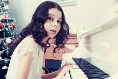 Bella ragazza in un vestito bianco che si siede al piano Fotografia Stock Libera da Diritti