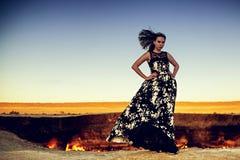 Bella ragazza in un vestito in bianco e nero sull'orlo di un abisso ardente fotografie stock libere da diritti