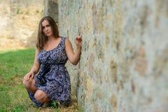 Bella ragazza in un vestito che si siede sui precedenti della parete della fortezza fotografie stock