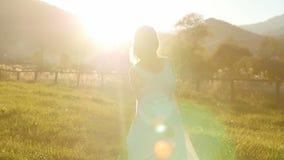 Bella ragazza in un vestito, filante al tramonto stock footage