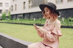 Bella ragazza in un vestito rosa che si siede vicino ai grattacieli La ragazza parla dal telefono Donna con capelli rosa in un bl immagini stock