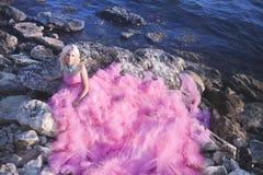 Bella ragazza in un vestito rosa sull'oceano in un vestito rosa fotografia stock