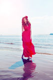 Bella ragazza in un vestito rosso luminoso dal mare Contro il BAC Fotografie Stock