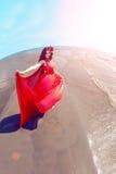 Bella ragazza in un vestito rosso luminoso dal mare Contro il BAC Fotografia Stock Libera da Diritti