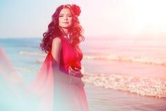 Bella ragazza in un vestito rosso luminoso dal mare Contro il BAC Immagine Stock Libera da Diritti