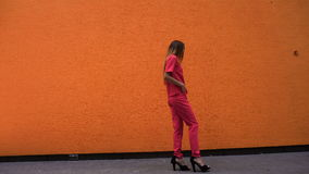 Bella ragazza in un vestito rosso nella camminata dei tacchi alti stock footage