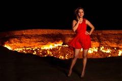 Bella ragazza in un vestito rosso sull'orlo di un abisso ardente immagine stock