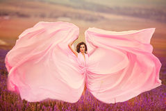 Bella ragazza in un volo rosa del vestito in un giacimento della lavanda Fotografia Stock