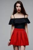 Bella ragazza in una blusa nera ed in una gonna rossa Fotografia Stock Libera da Diritti