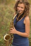 Bella ragazza in una maglietta blu che gioca il sassofono in oro o fotografie stock libere da diritti